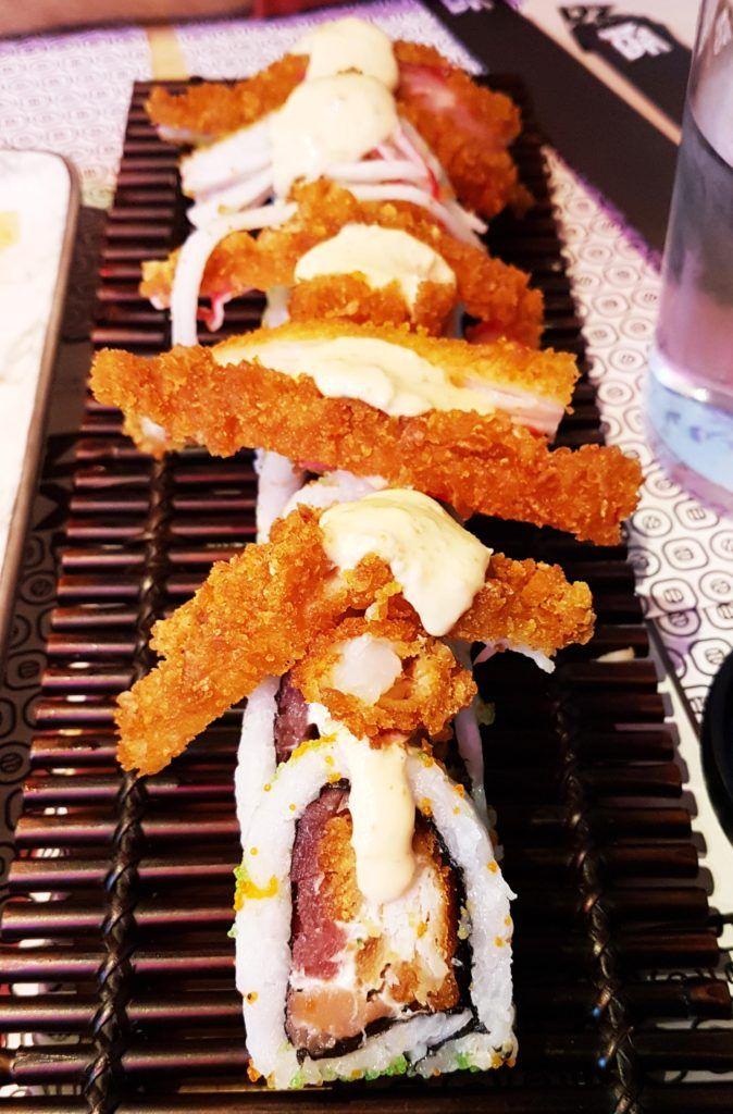 Yakuza Roll - Sushi Yakuza. Atún, salmón, merluza crunch, langostino tempura, cangrejo crunch, queso crema, cebollino, masago, salsa de anguila, salsa dinamita.